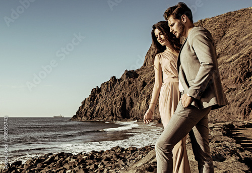 Foto op Canvas Artist KB Portrait of an attractive couple looking at the ocean's wave