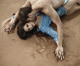 Portrait of a young sensual couple laying on the sand - 188597118