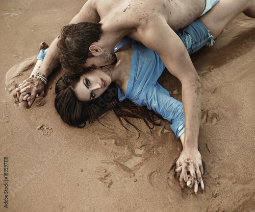 Fotobehang Konrad B. Portrait of a young sensual couple laying on the sand