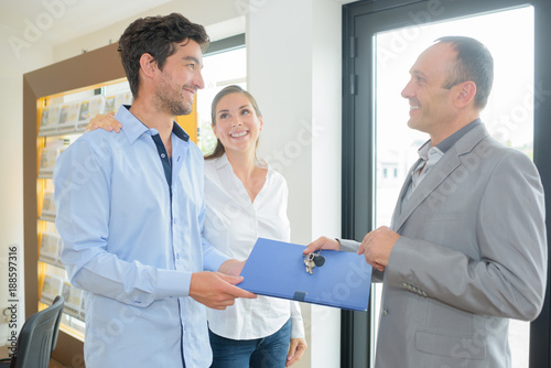 Estate agent passing file and keys to couple