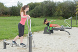 women exercising on a sport machine in outdoor gym - 188599106