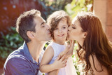 Happy parents kissing their beloved child - 188600901