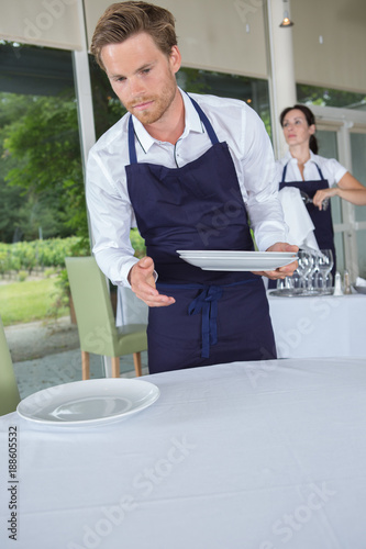 server in the restaurant holding the plates