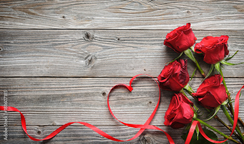 Leinwandbild Motiv Romantic floral frame with red roses and ribbon on wooden background
