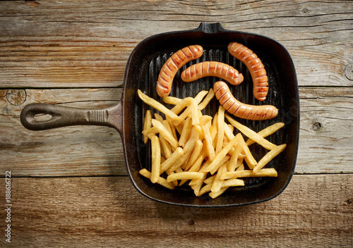 Foto Murales meat sausages and fried potatoes on cast iron pan