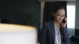 Young Asian businesswoman standing with luggage in hotel apartment and talking on mobile phone - 188649527
