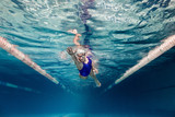 underwater picture of female swimmer in swimming suit and goggles training in swimming pool