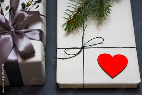 Foto Murales A gift box of craft paper tied with a lace. A wooden red heart.