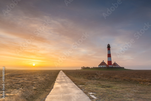 Sunrise at the lighthouse, a path seems to lead between the sun and lighthouse t Poster