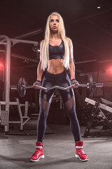 Young beautiful girl athlete bodybuilder at the gym doing exercises for the biceps using the barbell, in beautiful sportswear. Personal trainer. Dark background.