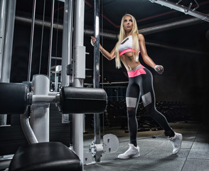 Young beautiful blonde girl doing exercises in the gym, wearing beautiful sportswear on a dark background.