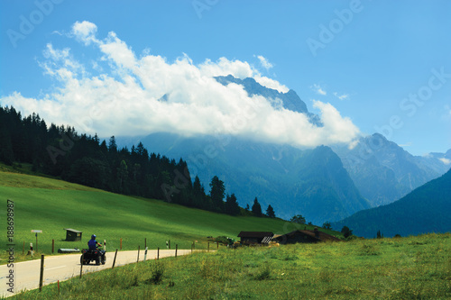 Fotobehang Blauw Road leading through alpine meadows to blue mountain top covered with cloud