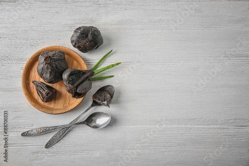 Aluminium Kruiden 2 Plate with black garlic (Allium sativum) on wooden table