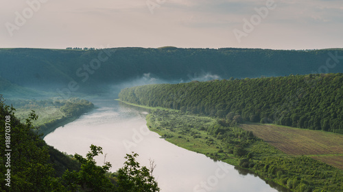 Fotobehang Groen blauw Top view of Dnestr river at sunrise. River is covered with mist and surrounded with green forest and fields.