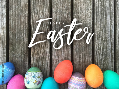 Happy Easter Calligraphy Text Message with Colorful Decorated Eggs Over Rustic Wooden Background