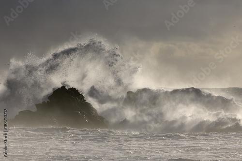 Stormy waves splash at sunset - 188710712