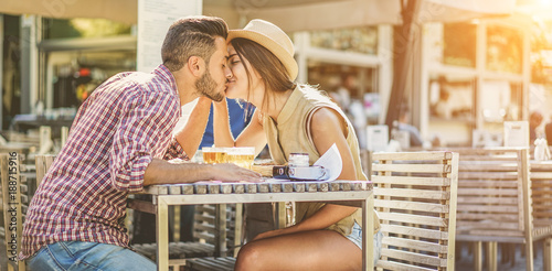 Happy travel couple kissing in bar restaurant for date dineer - Young lovers kissing having tender moments on summer vacation - Love, holidays, happiness and relationship concept - Focus on faces