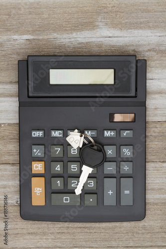 Calculator with house key on weathered wood - 188716146