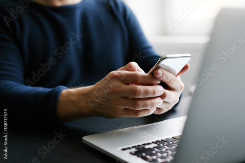 Foto Murales Man with mobile phone and laptop in office