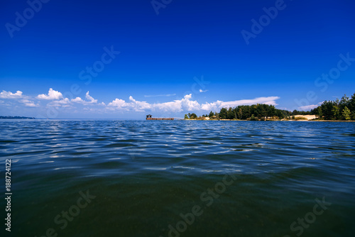 Fotobehang Donkerblauw blue sky with white clouds over water on a summer day