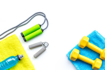 Fitness concept. Dumbbells, towel, sport drink, jump rope on white background top view copy space © 9dreamstudio