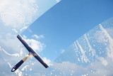 Rubber squeegee cleans a soaped window and clears a stripe of blue sky with clouds, concept for tranparency or spring cleaning, copy space in the background - 188731926