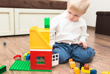 A little cute boy is an elementary school student lying on a wooden floor and playing cubes toys.  - 188736380