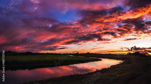 Foto op Plexiglas Aubergine Red sunset sky near the river