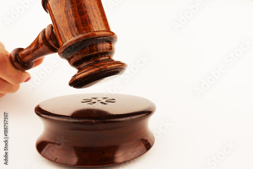 Justice concept or symbol with wooden judge gavel in woman hand, isolated on white background