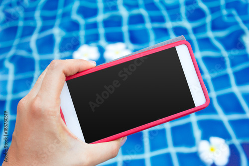 Smartphone with black screen near pool. Vacation concept
