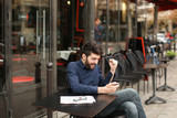 American boy listening to music at cafe with earphones and smart - 188782175