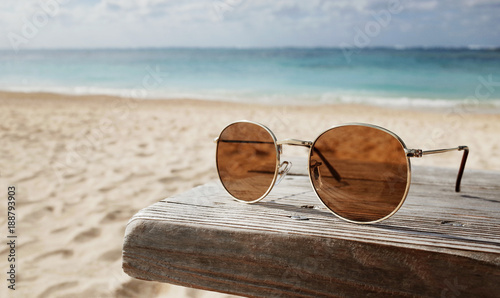 Sunglasses on Wooden Chair on The Beach in Holiday