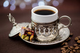 Traditional Turkish coffee in traditional metal cup on brown background with Turkish delight and bokeh