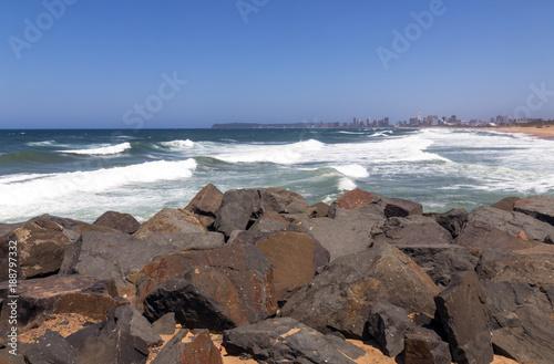 Foto Murales Rocks Against Beach Sea and Blue Durban City Skyline