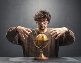Man raising his hands above the globe - 188804995