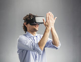 Young man playing in virtual reality goggles - 188805764