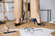 cropped shot of businesswoman standing near smartphone, papers and eyeglasses on floor