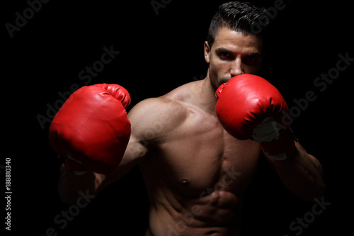 Muscular boxer portrait, isolated on black background