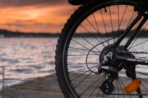 Fotobehang Fiets Mountain bike standing on a wooden bridge with lake and sunset in the background - selective focus