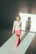 high angle view of beautiful blonde woman in trendy pink clothes walking in studio