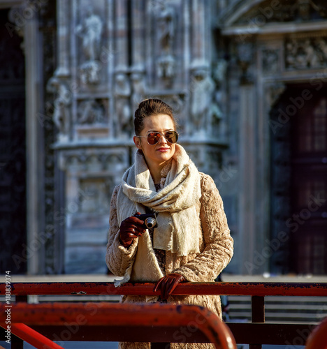 Keuken foto achterwand Milan tourist woman looking into distance while holding photo camera