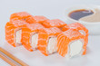 Delicious Philadelphia sushi rolls with rice, cream cheese and salmon on light background