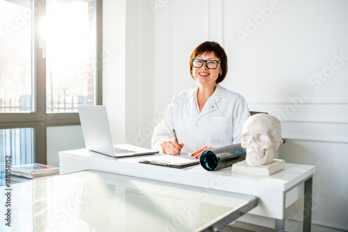 Portrait of a senior woman doctor working with laptop and documents in the beautiful white office interior
