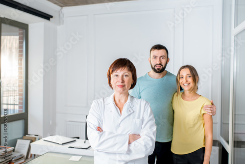Portrait of a senior woman doctor standing with young couple of patients in the white office