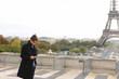 Arabian groom talking on smartphone near Eifel Tower in slow mot