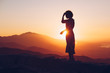 Woman Silhouetted Against Sunset on Mountains