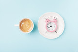 Morning cup of coffee and alarm clock on blue working desk top view. Breakfast time concept. Flat lay style.