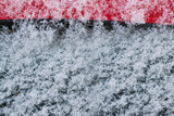 White snowflakes, snow on the black glass and red metal, abstract winter background