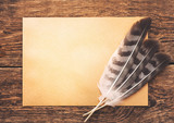 Paper with feather on the background of an old wooden table