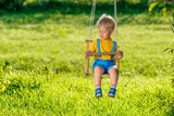 Rural scene with toddler boy swinging outdoors. - 188905735